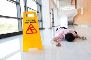 man on ground by wet floor sign