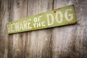 A beware of dog sign on fence.