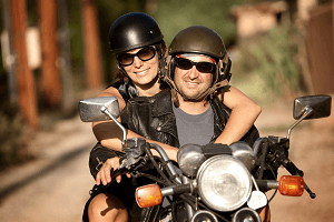 A guy rides a motorcycle with a girl in seat behind him.