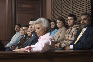 Jurors stare intently from the jury box as if listening to testimony.