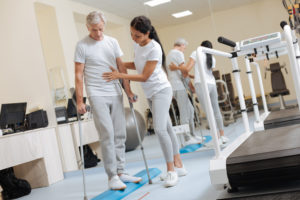A physical therapist helps a man on crutches in a rehab facility.